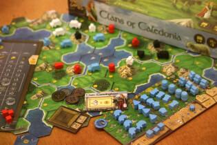 Spielplan mit Schachtel, Markttableau und Spielertableau- Clans of Caledonia