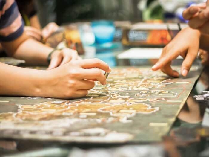 Hände über einem Spielbrett mit einer aufgedruckten Landkarte