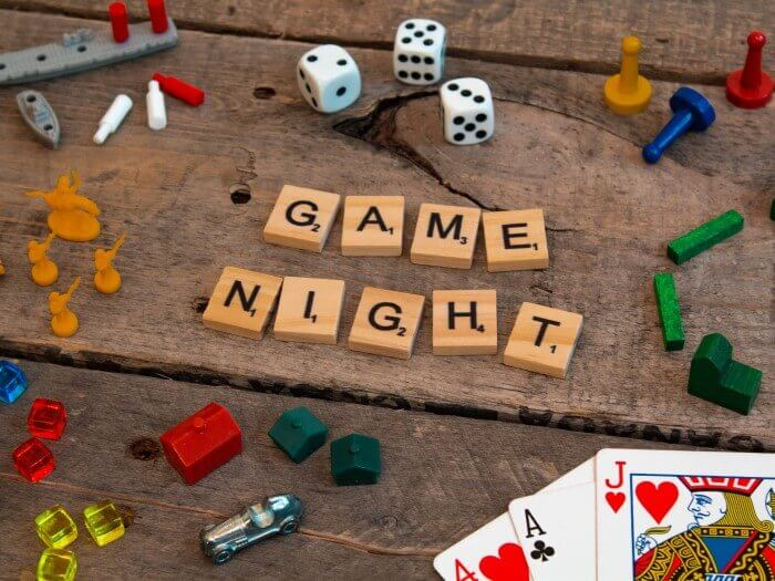Unterschiedliches Spielmaterial -  Scrabble Buchstaben, Würfel, Figuren, Gebäude, Karten