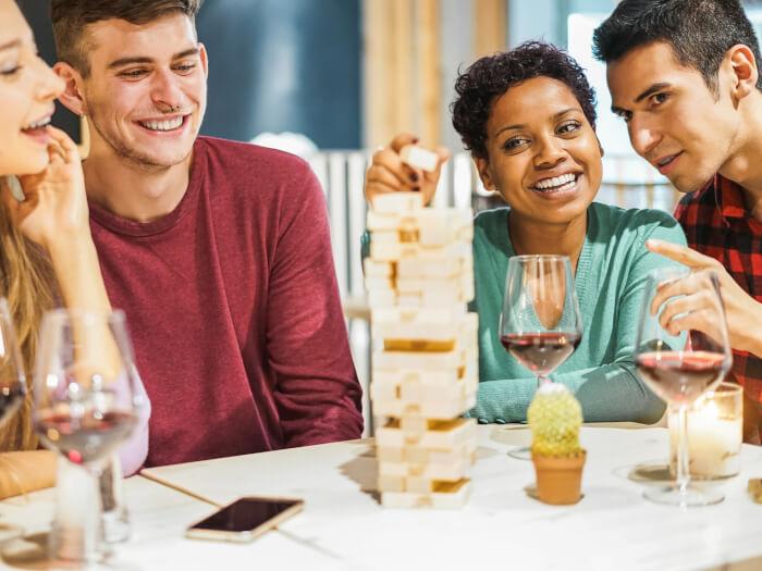 Freundesgruppe bei Spiel mit Getränken - Jenga